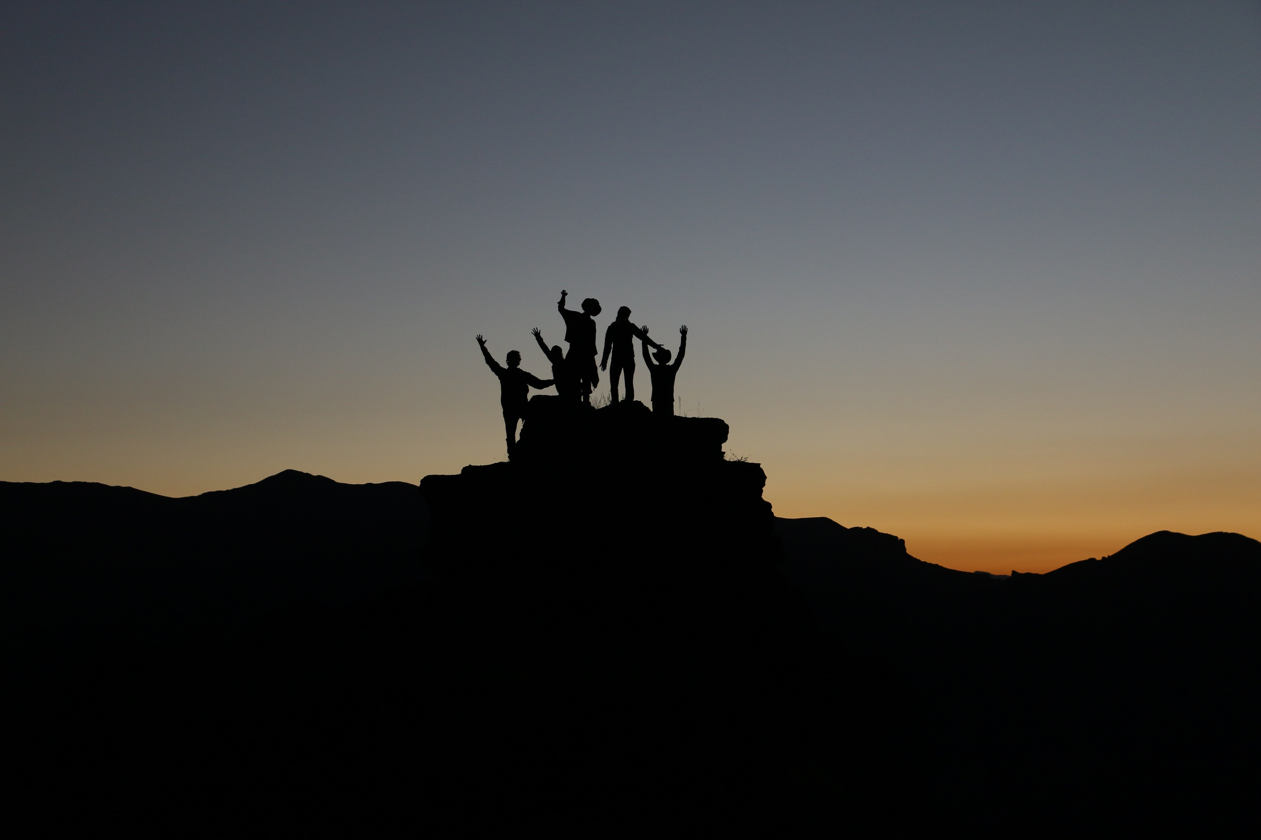 Silhouette of people posing on top of a rocky landscape